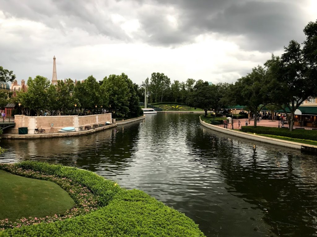 A water feature outside at Disney World with gray skies, and the sun still shining.