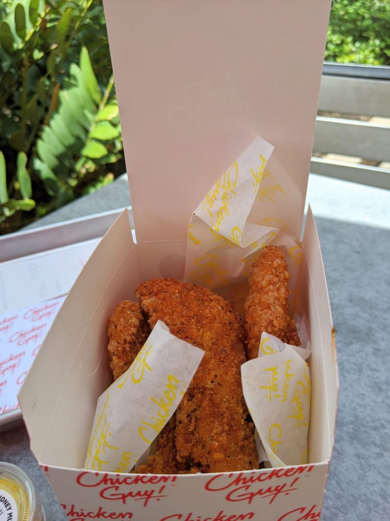 All-natural chicken tenders in a white to-go container with restaurant logo printed on the outside