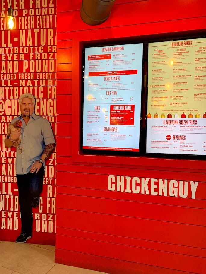 Digital menu boards on a red wall at Chicken Guy! in Disney Springs.